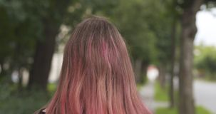 Teen girl from behind on sidewalk in town and wind blows her hair Stock Image