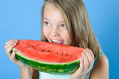 Teen girl bites a ripe juicy watermelon. Stock Image