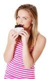 Teen girl biting a chocolate bar. Royalty Free Stock Photography