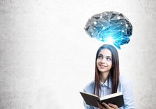 Teen girl with black book and brain hologram Stock Photography