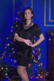 Teen girl in a black dress. Teen girl in Christmas at the beautiful Christmas tree glowing in the dark Stock Photo