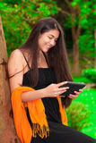 Teen girl in black dress outdoors using tablet computer Royalty Free Stock Photos