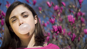 Teen girl blowing bubblegum bubble Stock Images