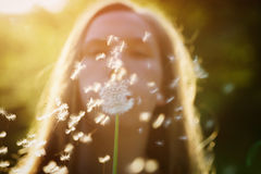 Teen girl blowing dandelion to the camera. Focus on girl royalty free stock photos