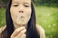 Teen girl blowing on a dandelion toning Stock Images