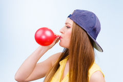 Teen girl blowing red balloon. Stock Image