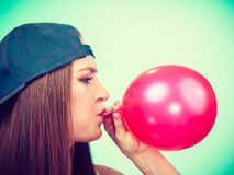Teen girl blowing red balloon. Stock Images