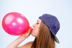 Teen girl blowing red balloon. Royalty Free Stock Images