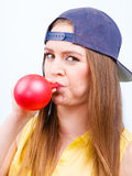Teen girl blowing red balloon. Royalty Free Stock Photography
