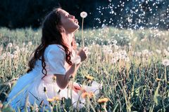 Teen girl blowing seeds from a flower dandelion in spring park. Teen girl blowing seeds from a flower dandelion in a spring park Royalty Free Stock Images