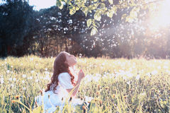 Teen girl blowing seeds from a flower dandelion in spring park Stock Photos