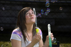 Teen girl blows bubbles Stock Image