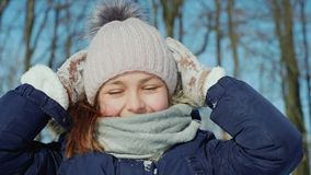 Teen girl blows snowflakes from knitted mittens in winter time. Teen girl blows snowflakes from knitted mittens. Beauty joyful teenage girl having fun in winter stock video footage