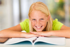 Teen girl book. Happy teen girl lying on book at home Stock Photography