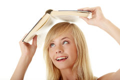 Teen girl with book over her head. Isolated on white Stock Photos