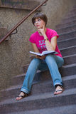Teen girl with book on the stairs Stock Photos