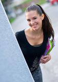 Teen girl with books. Girl with school books hiding behind the wall Stock Images