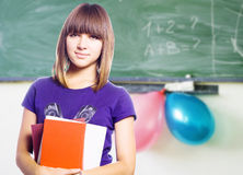 Teen girl with books. In hand against the blackboard Stock Images
