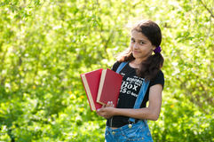 Teen girl with books on nature Stock Photo