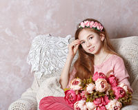 Teen girl with a bouquet of flowers. Beautiful teen girl with a bouquet of spring flowers in home interior royalty free stock photo
