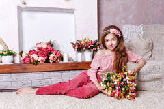 Teen girl with a bouquet of flowers. Beautiful teen girl with a bouquet of spring flowers in home interior. Barefoot girl sitting on the floor. The concept of a royalty free stock image