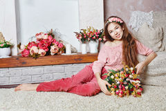 Teen girl with a bouquet of flowers. Beautiful teen girl with a bouquet of spring flowers in home interior. Barefoot girl sitting on the floor. The concept of a stock images