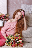 Teen girl with a bouquet of flowers. Beautiful teen girl with a bouquet of spring flowers in home interior. The concept of a happy childhood royalty free stock photography