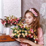 Teen girl with a bouquet of flowers. Beautiful teen girl with a bouquet of spring flowers in home interior. The concept of a happy childhood royalty free stock image