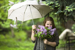 Teen girl with a bouquet of lilacs, standing under an umbrella. Royalty Free Stock Images
