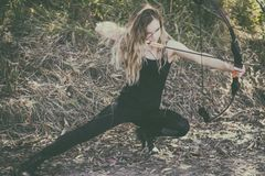 Teen girl with bow and arrow. Young teen blonde archer girl with a bow and arrow Royalty Free Stock Photography