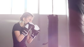 Teen girl in boxing gloves is working out a blow. Slow motion