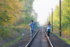 Teen girl and boy balancing on rails Stock Photo