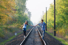 Teen girl and boy walking on rails Stock Image