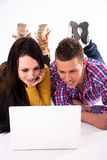 Teen girl and boy with white laptop Royalty Free Stock Photography