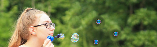Teen girl-bubble banner. Teen girl in the park blowing bubbles -banner-narrow Royalty Free Stock Image