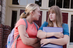 Teen Girl Bully. An aggressive teen girl intimidates another girl in front of their school, probably over a boy Royalty Free Stock Photography