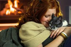 Teen girl with cat at home. Happy teen girl caressing cat at home, affectionate moment royalty free stock images
