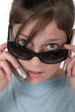 Teen Girl With Cellphone 6a. Cute tween or young teenage girl looking over sunglasses and talking on a cellphone; shot on white Royalty Free Stock Photography