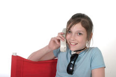Teen Girl With Cellphone 8a. Cute tween young teenage girl sitting in a chair and talking on a cellphone; shot on white Stock Images