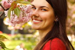 Teen girl charming happy smiling in garden. Teen girl charming happy smiling in nature garden Japanese cherry tree Royalty Free Stock Image