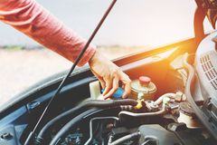 Teen girl check the engine radiator of the car. For trip travelling in holiday Stock Photo
