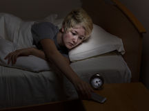 Teen girl checking cell phone late at night while in bed Royalty Free Stock Images