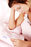 Teen girl checking pregnant test. Teen pretty depressed girl checking her pregnant test in bed stock photography