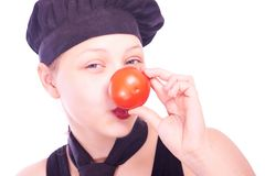 Teen girl in chef hat with tomatoes Stock Photo