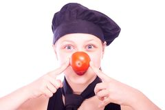 Teen girl in chef hat with tomatoes Stock Photography