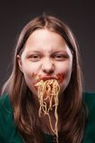 Teen girl chewing pasta Royalty Free Stock Photography