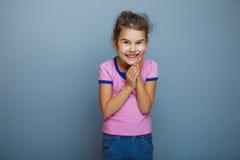Teen girl child is happy surprise on gray. Teen girl child is happy surprise on a gray background Stock Image