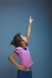 Teen girl child pointing at the sky on gray Royalty Free Stock Photography