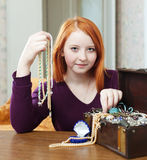 Teen girl chooses bead in treasure chest Stock Images