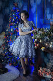 Teen girl in Christmas at the beautiful Christmas tree g. Lowing in the dark Royalty Free Stock Photos